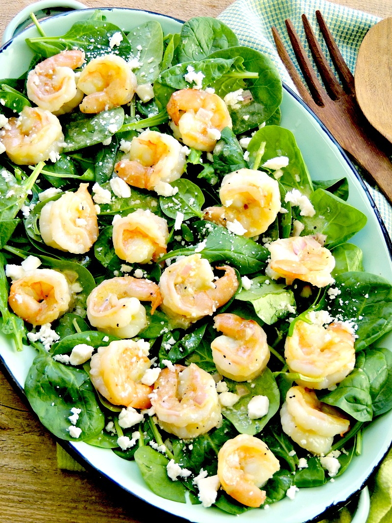 Shrimp Spinach Salad with Feta on a teal enamel platter with a wood background and green towel.