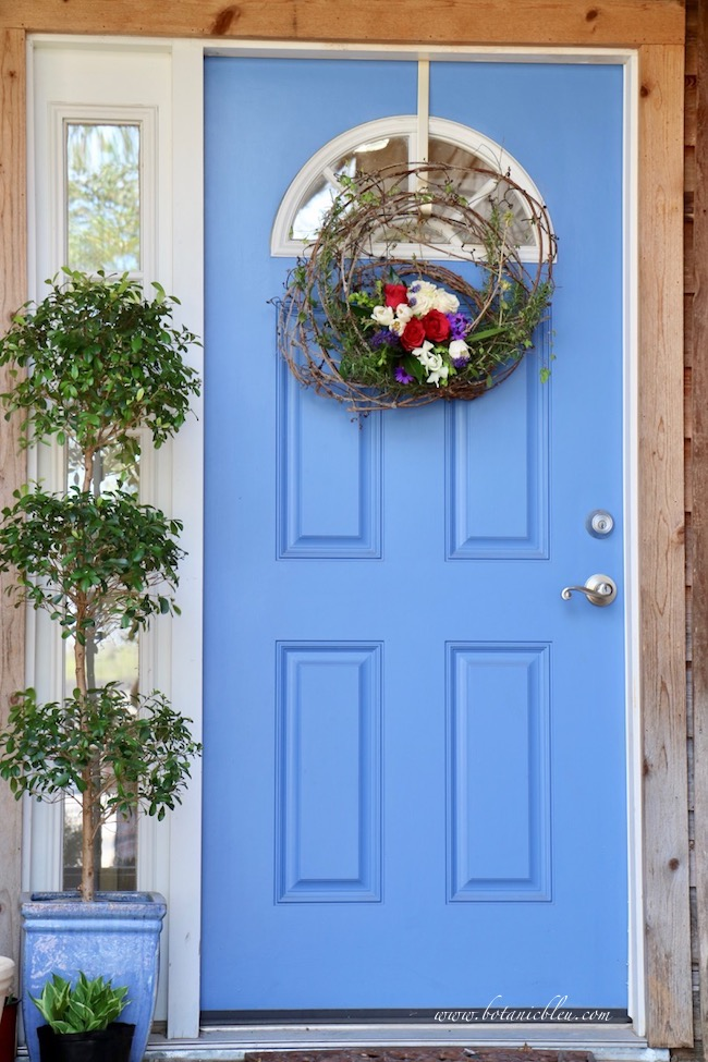 front porch with live floral grapevine wreath on blue front door and topiary plant