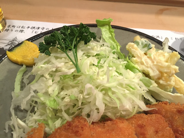 a close up photo of the best Tonkatsu in Tokyo with lots of shredded cabbage