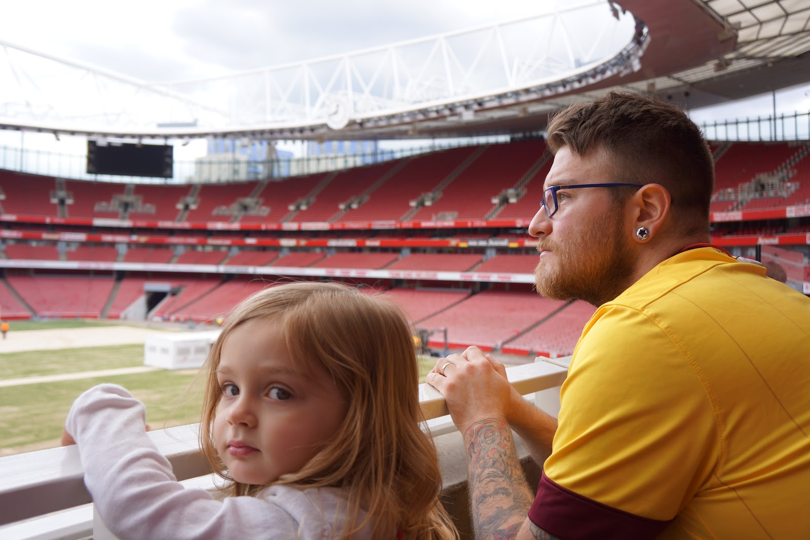 dad and daughter looking at Arsenal Stadium  pitch