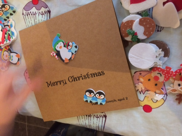 Toddler sticking Christmas stickers to card