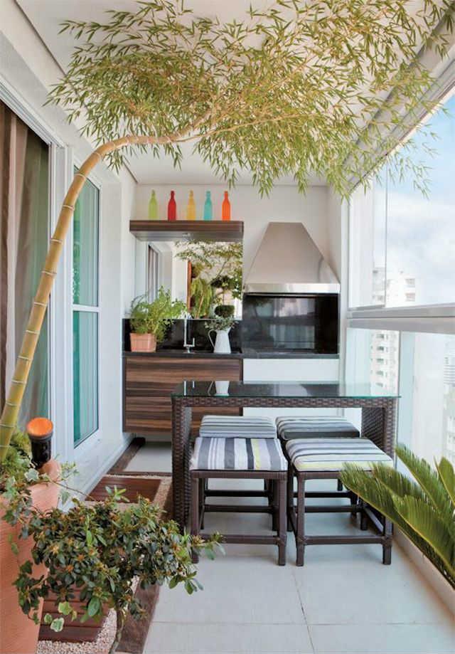 Balcón cerrado con cocina integrada, comedor y barbacoa.