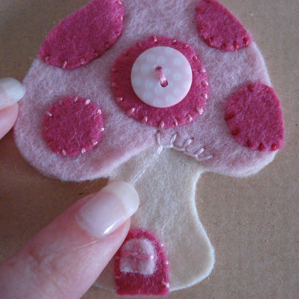 Sewing blanket stitch along the pink felt mushroom ornament design
