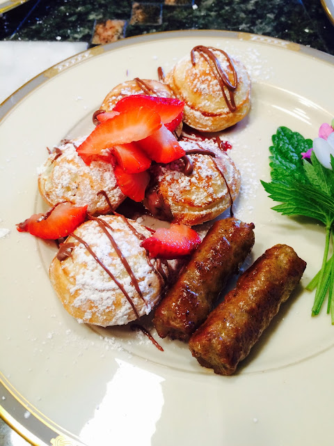 plate with ebelskivers (round filled pancakes) drizzled with Nutella and strawberries