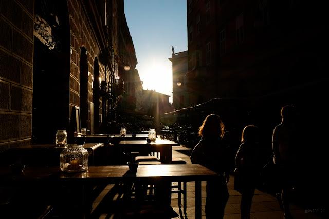 Fotografia in controluce dei locali in una strada di Trieste