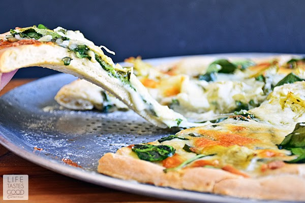 Spinach Artichoke Pizza Recipe | by Life Tastes Good is like eating one of your favorite dip recipes in pizza form! The crust is smothered in an easy-to-make, creamy white Gruyere cheese sauce and then topped with fresh spinach, marinated artichoke hearts, and even more cheese. This pizza smells so good while baking and tastes even better! #SundaySupper