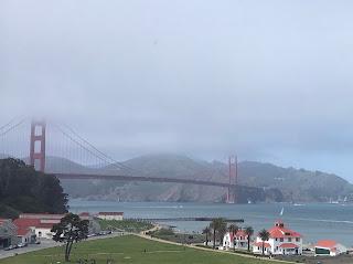 Lang hengebro over et sund. Tårnene på broen stikker opp i skyene.