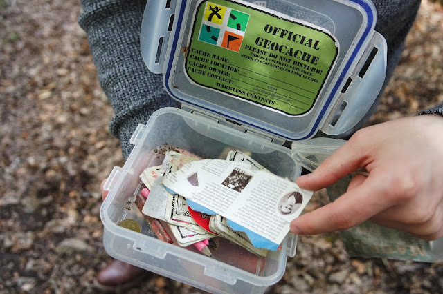 a geocache box containing pennies, cards, and papers