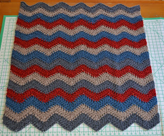 Speedy Ripple Blanket on blocking board. Chunky yarn, 6-ripple stripes in grey, beige, blue and red.