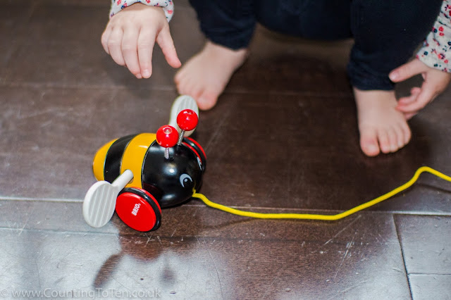 A colourful bumble bee toy with a child reaching for it.