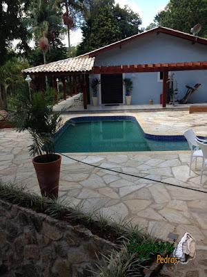 Construção da piscina em alvenaria com revestimento de azulejo, o piso do passeio da piscina com pedra São Tomé tipo caco em residência em Atibaia-SP com o pergolado de madeira.