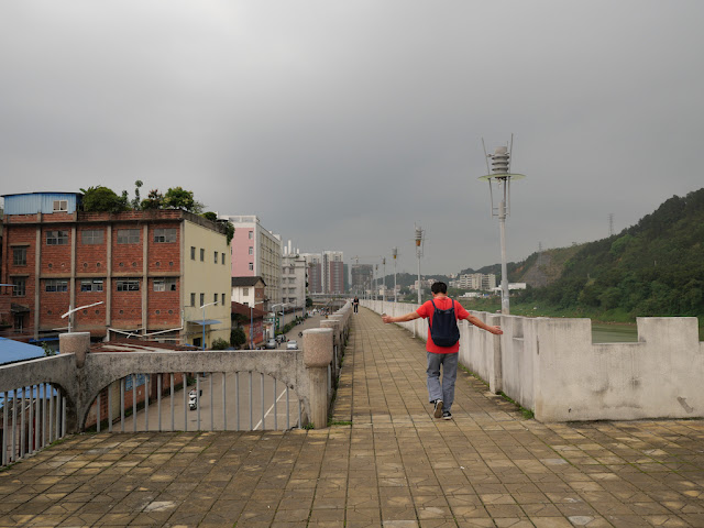 man walking with outstretched arms on a wall bordering the Gui River (桂江) in Wuzhou (梧州)