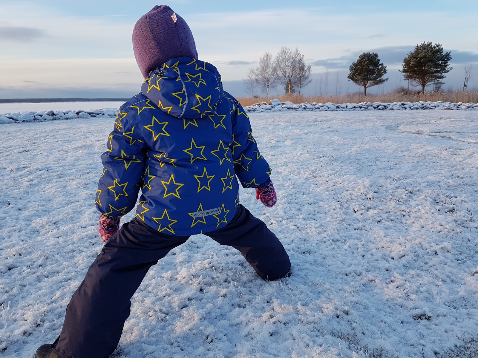 three year old wearing muddy puddles ski clothing