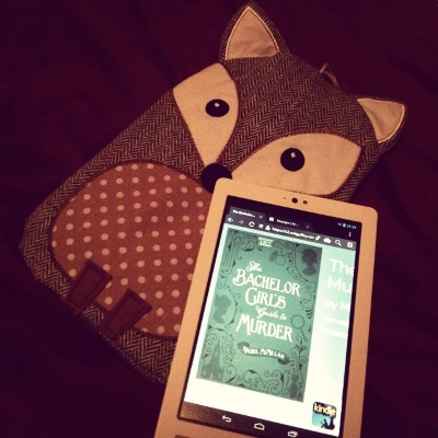 A white Kobo with The Bachelor Girl's Guide to Murder's green cover on its screen lies across a water bottle with an adorable grey herringbone fox cover. The fox has wide white eyes and a brown belly with beige polka dots. The book's cover features female silhouettes in darker green, with a magnifying glass, a cat, and a church worked into the border.