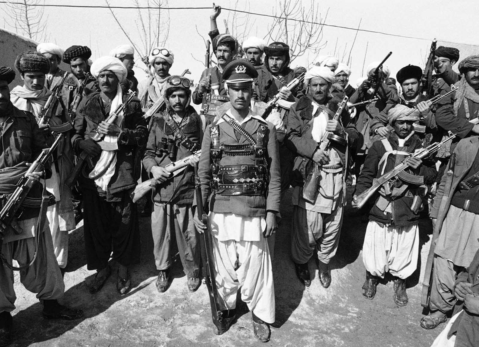 A mujahideen, a captain in the Afghan army before deserting, poses with a group of rebels near Herat, Afghanistan, on February 28, 1980. At the time, it was reported that the Afghan capital of Kabul returned to normal for the first time since bloody anti-Soviet rioting erupted there, killing more than 300 civilians and an unknown number of Soviet and Afghan soldiers.