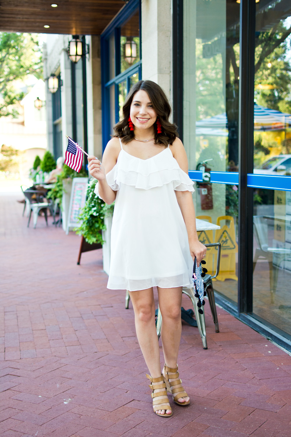 White cold shoulder dress paired with red statement earrings and a pom pom clutch styled for July fourth