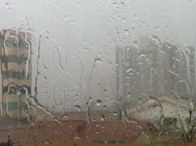 Respingos de chuva na vidraça pode inspirar uma arte abstrata, pode ser adaptada com texturas, mudar as cores, colocar ponto de luz nas janelas do prédio.
