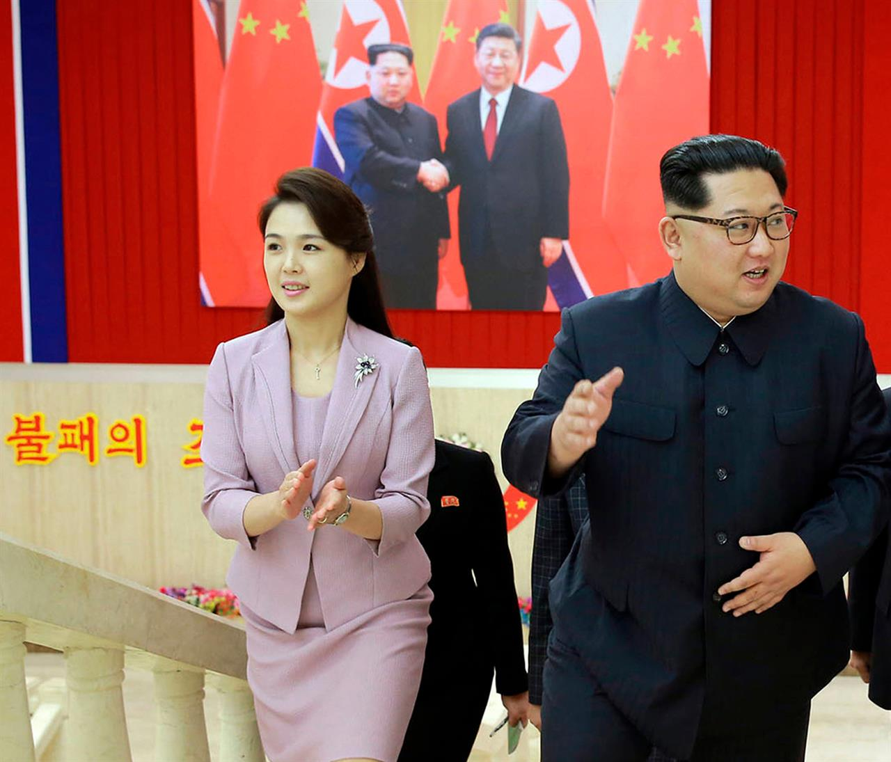 In this April 14, 2018, file photo provided by the North Korean government, Ri Sol Ju claps while walking with her husband, North Korean leader Kim Jong Un, right, in Pyongyang, North Korea.