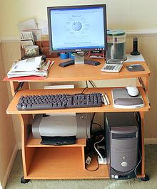 Un computador personal de escritorio mostrando la Wikipedia con una impresora conectada