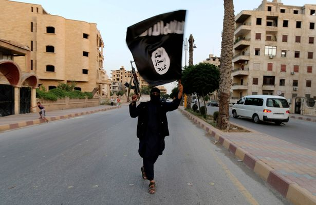 PROD-A-member-loyal-to-the-ISIL-waves-an-ISIL-flag-in-Raqqa