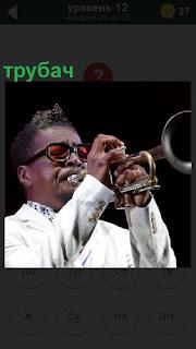 Мужчина в белом костюме трубач исполняет музыкальную композицию