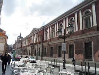 Gran dificio de estilo neoclásico, de dos plantas. En la superior, columnas en relieve enmarcan las ventanas.