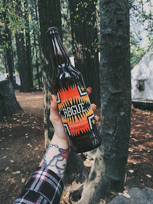 A picture of a woman holding a bottle of Rogue x Pendleton beer