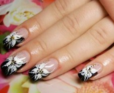 Foto de diseño de uñas con bellas flores de color blanco y negro