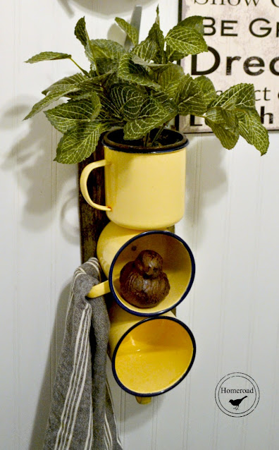 Yellow enamelware mug organizer filled with plants