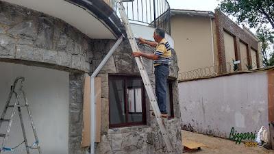 Bizzarri visitando uma obra e conferindo a execução dos trabalhos com pedra na restauração de um revestimento com pedra tipo folheta e folhetinha com paralelepípedo e conferindo a requadração nas janelas.