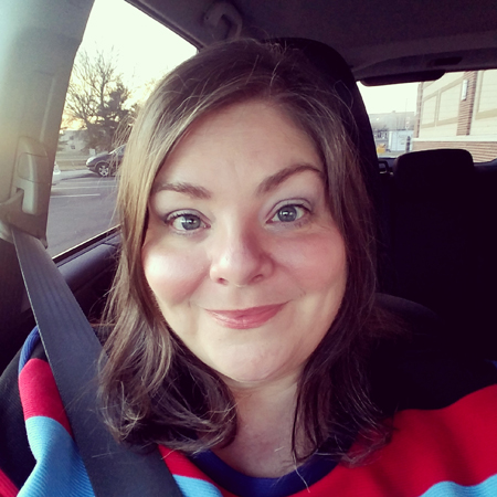 image of me from the shoulders up in the car, wearing a colorful stripey dress