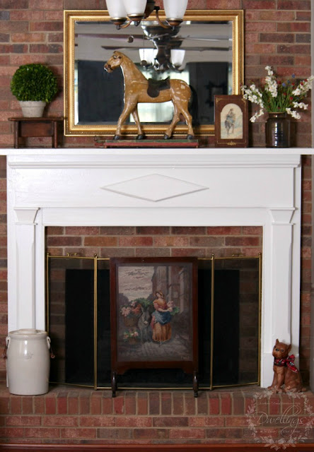 On the fireplace is an antique horse pull toy, old crock filled with flowers, a watercolor horse painting and a needlework fireplace screen with a lady gathering flowers and placing in them in a basket on the back of a donkey.
