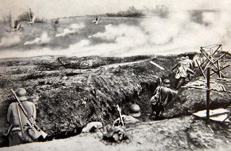 Cette image représente le champ de bataille de la bataille de Verdun : on peut y voir un paysage dévasté et fumant, avec au premier plan une tranchée à l'intérieur de laquelle se tiennent des hommes debout, armés et en uniforme, certains en train de courir. Le fait que la photo soit en noir et blanc ajoute encore à l'aspect désolé et morne du paysage; Quelques informations sur cette fameuse bataille afin de la resituer : La bataille de Verdun fut une bataille de la Première Guerre mondiale qui eut lieu du 21 février au 19 décembre 1916 près de Verdun en France, opposant les armées françaises et allemandes. Conçue par le général von Falkenhayn, commandant en chef de l'armée allemande, comme une bataille d'attrition pour « saigner à blanc l'armée française »1 sous un déluge d'obus dans un rapport de pertes de un pour deux, elle se révélera en fait presque aussi coûteuse pour l'attaquant : elle fit plus de 300 000 morts (163 000 soldats français et 143 000 allemands) et se termina par un retour à la situation antérieure. Elle n'en constitue pas moins une grande victoire défensive de l'armée française, jugée a posteriori par les Allemands comme de même nature que la victoire de l'armée rouge dans la bataille de Stalingrad. Parallèlement, de juillet à novembre, l'armée britannique ainsi que l'armée française seront engagées dans la bataille de la Somme, tout aussi sanglante.  Alors que, côté allemand, ce sont pour l'essentiel les mêmes corps d'armée qui livreront toute la bataille, l'armée française fera passer à Verdun, par rotation, 70 % de ses Poilus, ce qui contribua à l'importance symbolique de cette bataille et à la renommée du général Pétain qui commanda la première partie de la bataille. C'est au général Nivelle que revint le mérite de l'enrayement définitif de l'offensive allemande (juin - juillet 1916), puis de la reconquête du terrain perdu entre octobre et novembre 1916 avec la récupération du fort de Douaumont, aidé en cela par son subordonné le général Mang