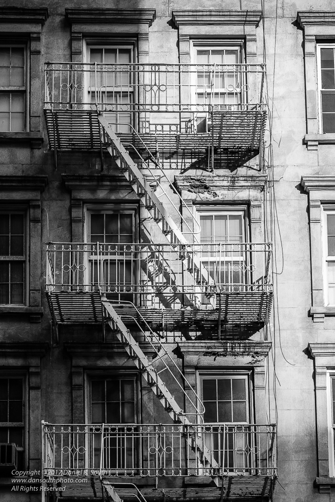 a photo in black and white of a fire escape in manhattan new york