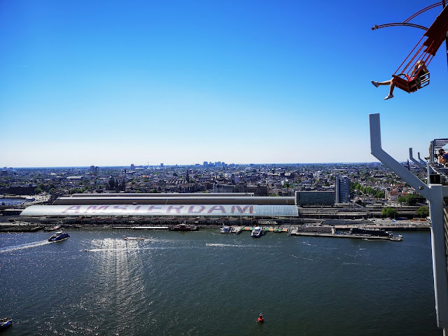 View Over Centraal Station From The ADAM Lookout Amsterdam. Showing the canal and people using a swing that extends beyond the lookout building.