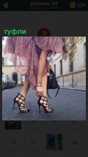 По мостовой идет девушка в туфлях и рукой поправляет ремешки на них
