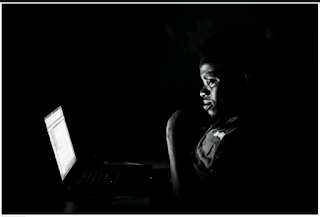 man in dark room infront of laptop