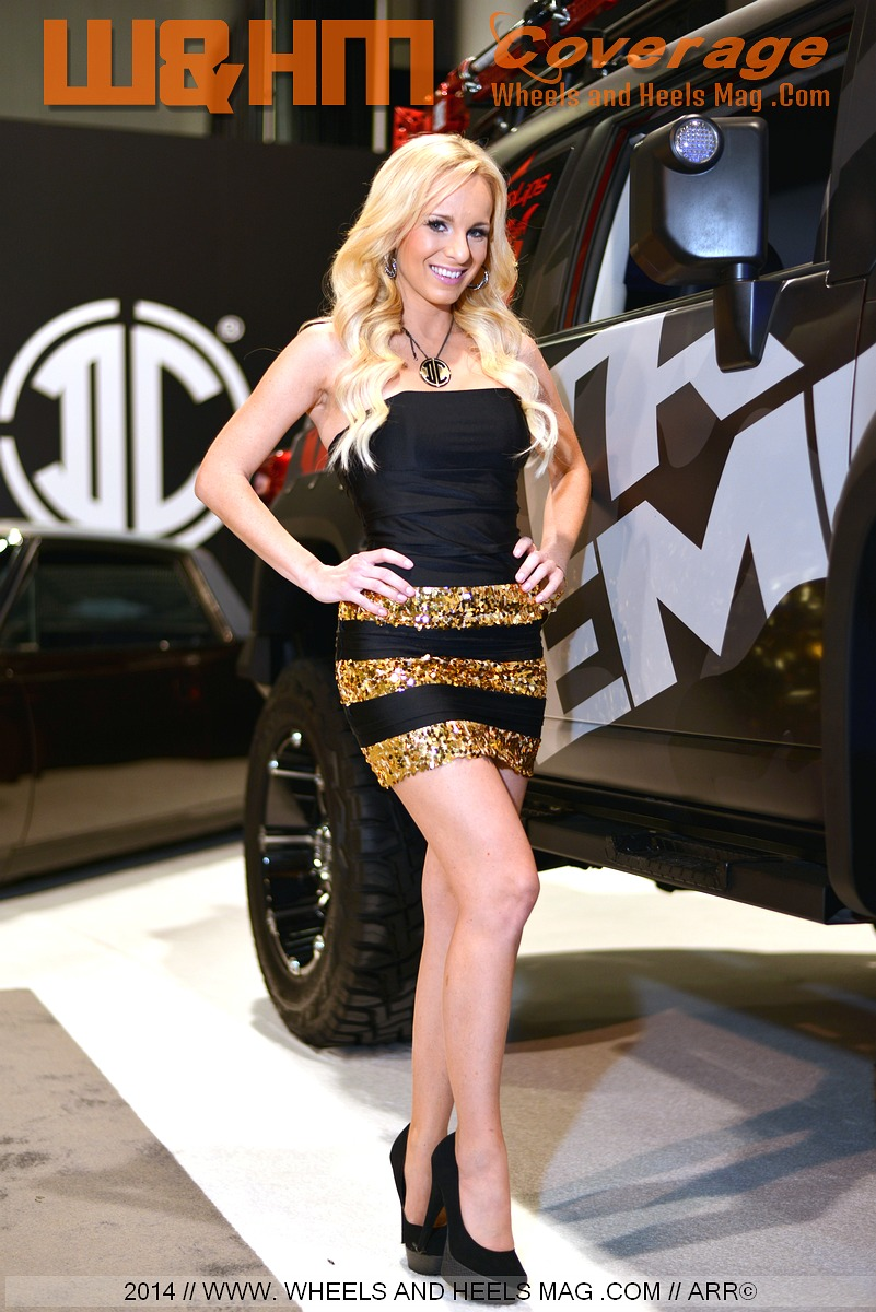 Sema models Dennii for 2Crave Wheels in sexy gold trimmed black minidress at 2014 SEMA show