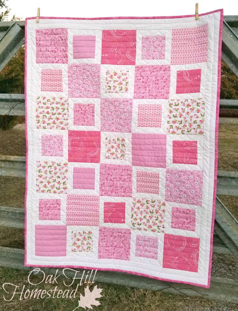 Large and small squares alternate in this girl-y crib quilt. (c) Oak Hill Homestead