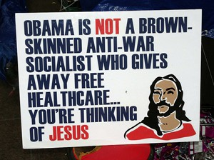 Political protest sign. 'Obama's not a brown-skinned anti-war socialist who gives away free healthcare. You're thinking of Jesus.' Quote by John Fugelsang. What SHOULD  take home message be? The best Christian vs Atheist debate ever! marchmatron.com
