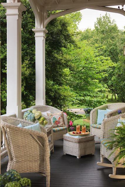 front porch of the main house with four wicker chairs and one foot stool with cushions and a tray on the foot stool with a plate with strawberries and two glasses of tea on it. lots of green trees in the background and potted blue plantes on the porch