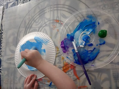 Toddler completing her paper plate planet craft.