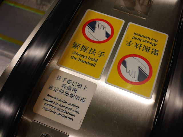 'Always hold the hand rail' and 'Anti-bacterial coating applied to handrail with addition disinfection regularly carried out' signs on an MTR escalator in Hong Kong