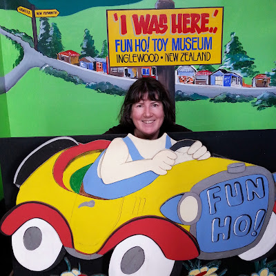 Woman posing in a cardboard car in front of a sign saying 'I was here...Fun Ho! Toy Museum'