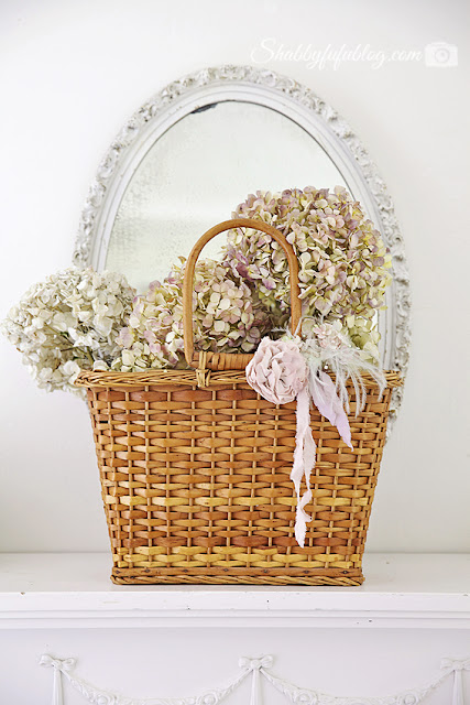 A vintage wicker basket with pastel Peony flowers in front of a white rimmed mirror - a beautiful and simple floral peony wreath display.