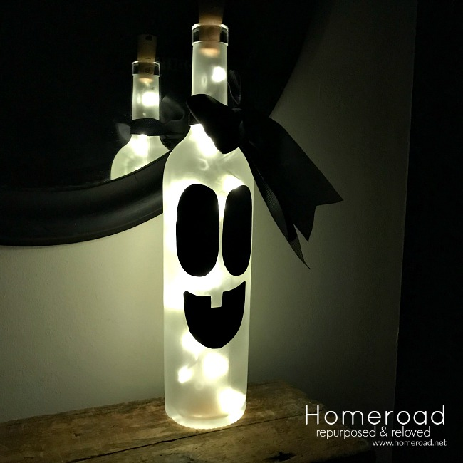 Ghost lighted wine bottle with face and bow