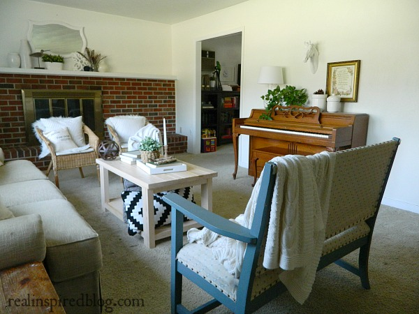 A cottage-like summer living room tour using whites, neutrals, and small pops of color in furniture and plants.