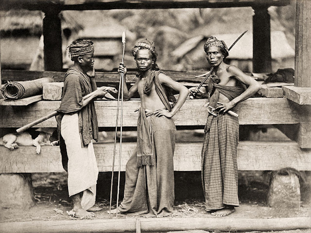 Three Batak warriors with spears and swords in front of a wooden construction. A dog lies between the two girders at the left. Circa 1870