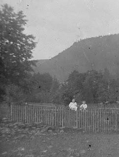 Ausschnitt - Zwei Personen im Garten vor einer Hügellandschaft - um 1900