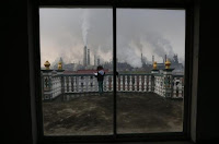 A girl reads a book on her balcony as smoke rises from chimneys of a steel plant, on a hazy day in Quzhou, Zhejiang province April 3, 2014. (Credit: Reuters/Stringer) Click to Enlarge.